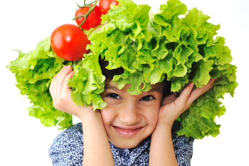 child using lettuce and tomatos as a hat
